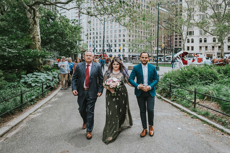 Photo of bold bride dressed in olive green dress walking down the Central Park aisle towards Cop Cot alongside her father and brother, while she's holding a beautiful bouquet