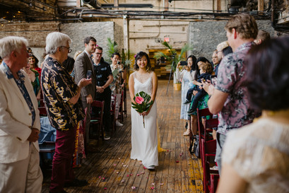 Smiling bride walks down the aisle holding a gorgeous tropical bouquet with pink floral as the guests stand up in her presence before the modern ceremony officiated by Once Upon A Vow begins in Greenpoint Loft