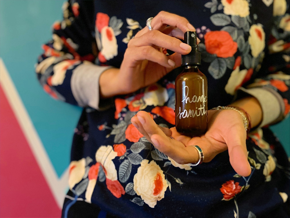 A close-up image of hands holding a homemade hand sanitizer made to cleanse hands during the coronavirus pandemic; person is wearing a floral sweatshirt against a pink and teal background