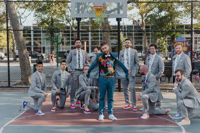 Group photo of groom in teal suit with tropical shirt and white bowtie surrounded by groomsmen dressed in light grey suits with varying colored converse sneakers in a basketball court set in Greenpoint Brooklyn. Groom is holding his blazer open and five out of the ten groomsmen are on one knee.