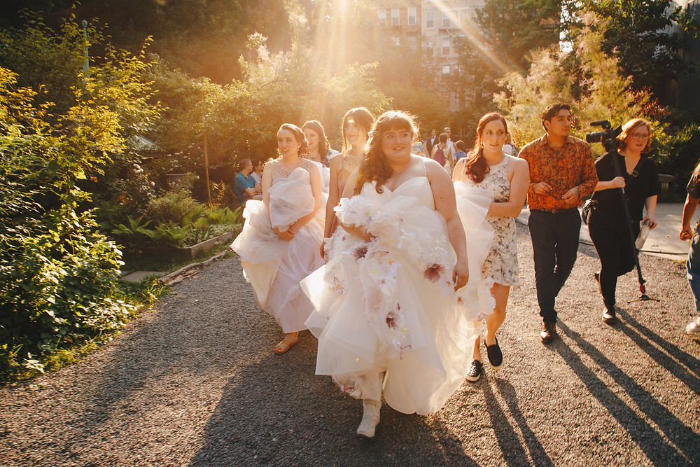Two brides walking in the park with their wedding crew holding the backs of their dresses to prevent them from dragging on their way to taking some pictures before the sun sets.