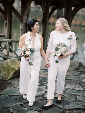 Asian-Canadian and Anglo-American brides walking hand in hand on the Wagner Cover stone pathway away from their ceremony gazebo; they're carry their bouquets; picture taken post elopement ceremony officiated by lgbtq+ officiant at Once Upon A Vow.