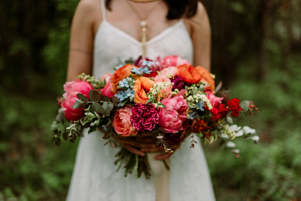 Vibrant, colorful, mostly pink bouquet designed by Ember Floral Co. being held by bride dressed in white with a v-neck and spaghetti straps with a golden necklace, now offering contactless wedding bouquet delivery across New York City