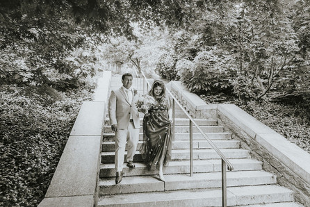 Black and white photo of bride and groom walking hold the stairs arm in arm in Central Park, post-ceremony led by modern NYC officiant from Once Upon A Vow