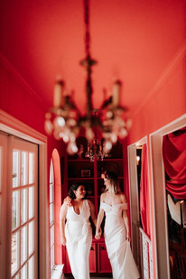 A femme LGBTQ couple smiling at each other as they walk down a rose painted hallway with out of focus chandelier; one marrier is wearing a v-neck white romper with a floral shoulder piece and the other is wearing an off the shoulder white dress with floral crown.