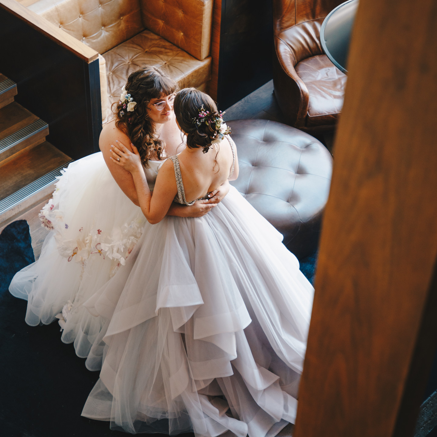 Two femme presenting queer white brides, both in dresses, one white with a playful leafy pattern in red and purple tones; the other wearing a champagne backless dress and showcasing an updo; looking into each other's eyes, they're thinking about their ceremony which will soon follow; officiated by queer officiant at Once Upon A Vow.