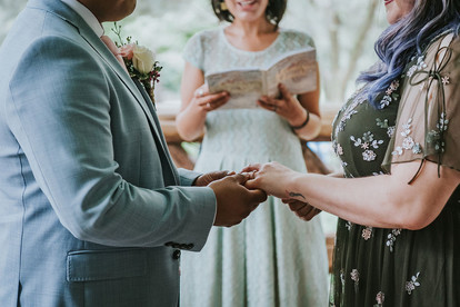 Close-up photo of the groom placing the wedding ring on the purple-haired bride's finger with a wrist tattoo with the Spanish-speaking wedding officiant wearing light blue from Once Upon A Vow in the background in Central Park's Cop Cot