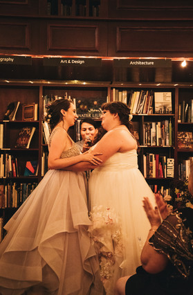 Two brides post embrace have their hands on each others arms and are looking at each other lovingly; queer officiant at Once Upon A Vow is on the verge of pronouncing them married.
