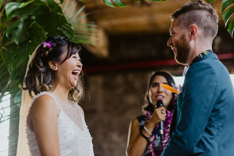 Photo of bride laughing and groom smiling as the wedding officiant from Once Upon A Vow speaks into the microphone addressing them before officially pronouncing them married in Greenpoint Loft, Brooklyn