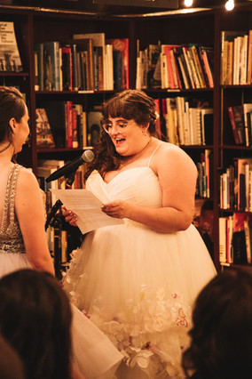 Bride in white dress is reading her personal vows to her bride; she's smiling as she's reading and surrounded by shelves full of books.