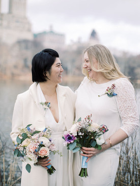 Close up of two brides smiling and giggling with each other; both wearing white and off-white tops with corsages and bouquets on display; picture taken post elopement ceremony officiated by gay officiant at Once Upon A Vow.