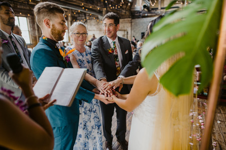 Photo of ring warming with couple and their parents, parents of the groom standing near their son and parents of the bride standing near their daughter, with modern officiant from Once Upon A Vow leading a meaningful moment of collectiveness slightly out of frame on the left with book in one hand and mic in the other in Greenpoint Loft, Brooklyn