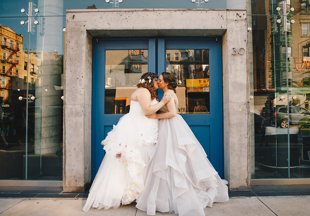 Two brides kissing in front of Downtown glass and stone building with blue doors; one is wearing a white dress; the other is more of a champagne color; picture taken before ceremony officiated by lgbtq+ officiant at Once Upon A Vow.