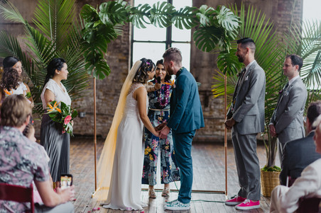 Photo of the couple leaning into the microphone at the same time while the fun and modern officiant from Once Upon A Vow asks them if they take each other to be husband and wife in Brooklyn's Greenpoint Loft