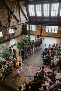 Aerial photo of ceremony officiated by modern officiant from Once Upon A Vow while the couple looks into each other's eyes and guests connect with the personalized ceremony in Brooklyn's Greenpoint Loft