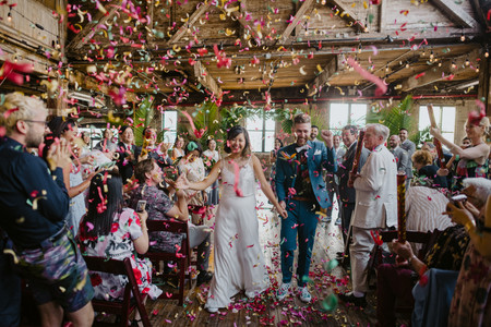 Bride and groom hold hands as they walk down the aisle as husband and wife with floral confetti bursting all around them after the officiant from Once Upon A Vow pronounced them married in Greenpoint Loft, Brooklyn