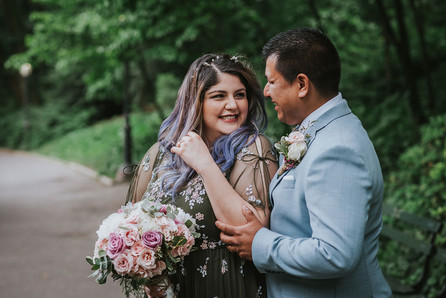 Candid photo of couple smiling at one another, the bride playing with her purple hair with her left hand while her right holds the bouquet as the groom in blue suit looks onward at her in Central Park