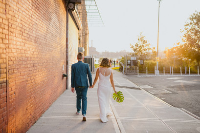 Photo of newly married husband and wife walking away from the camera down a Brooklyn sidewalk, groom on the left and bride on the right while they're holding hands and bride holds her tropical leaf bouquet, a red brick wall is to their left and the golden hour is to their right.