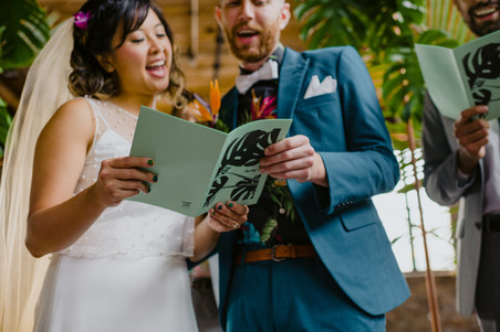 Close up photo of bride and groom holding their song sheet of a personalized song they wrote together for a group sing-a-long led by modern officiant from Once Upon A Vow in Brooklyn's Greenpoint Loft