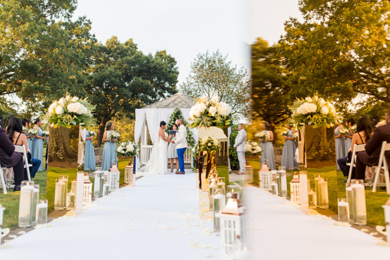 Wide shot of ceremony centering bride and groom holding hands during the bilingual wedding ceremony officiated by Once Upon A Vow at Pelham Bay Golf Course's gazebo, with candles and floral arrangements lining the aisle and seated guests watching