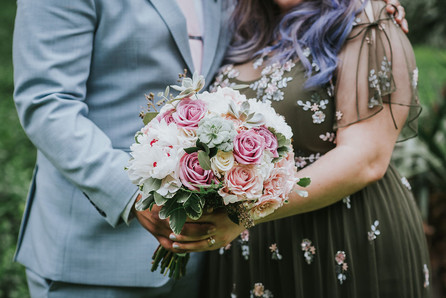Close-up photo of purple-haired bride in olive green sequined dress and groom dressed in blue-suit holding a white and pink bouquet post-ceremony led by NYC wedding officiant from Once Upon A Vow, in Central Park