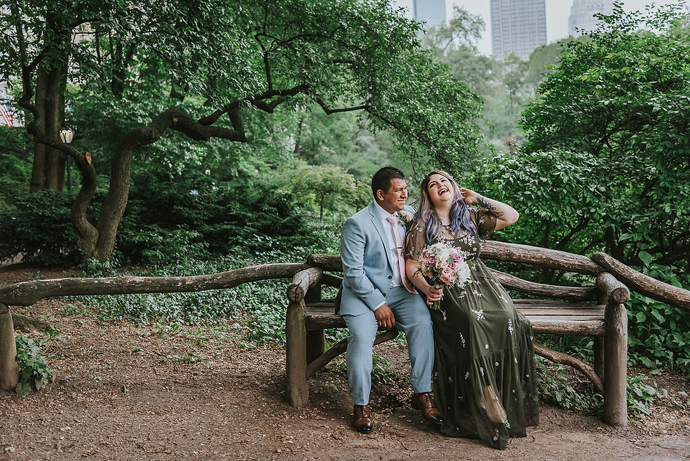 Happy just-married Latinx couple sitting on a wooden bench in Central Park post-ceremony officiated by Spanish speaking officiant from Once Upon A Vow, the groom is wearing a light blue suit with a pink tie and the bride wearing an olive green sequined dress is holding a bouquet, her left hand playing with her hair, while facing skyward with laughter