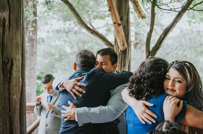 Photo of bride and groom hugging their parents smiling from ear to ear post-ceremony officiated by Spanish-speaking officiant from Once Upon A Vow in Cop Cot, Central Park