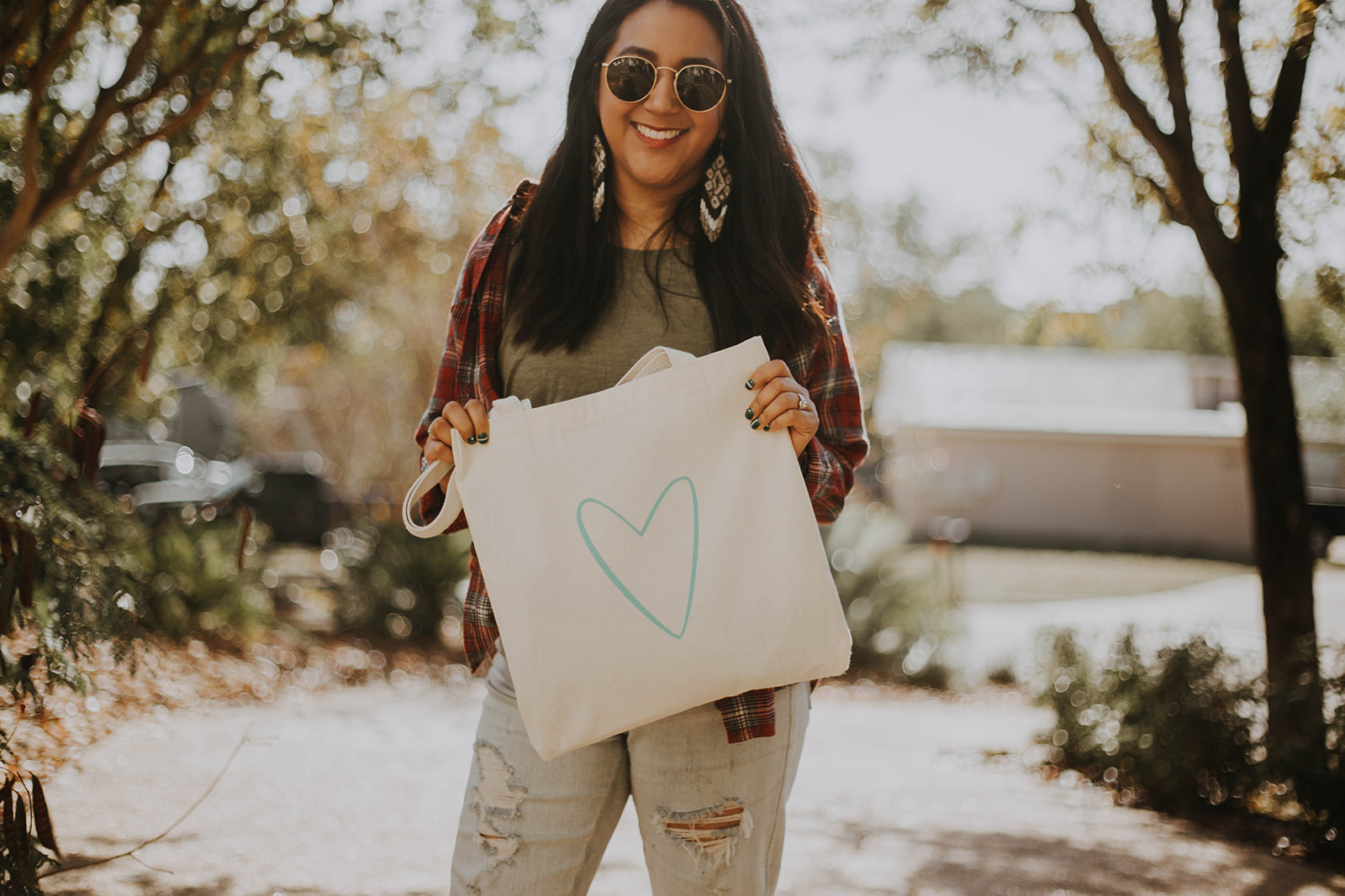 Smiling latina creative, Mary-Beth from Heart of Celebration, wearing dangly earrings and plaid shirt holding a tote bag with a blue heart on it representing the Radical Wed Retreat