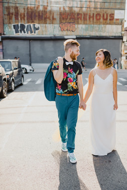 Photo of couple walking hand in hand down a Greenpoint Brooklyn sidewalk looking at each other and smiling; the groom is holding his teal suit blazer over his right shoulder