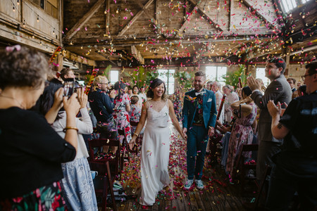 Post ceremony officiated by wedding celebrant from Once Upon A Vow of couple walking down the vibrant, colorful confetti smiling and laughing as the guests clap and take photos in Brooklyn's Greenpoint Loft