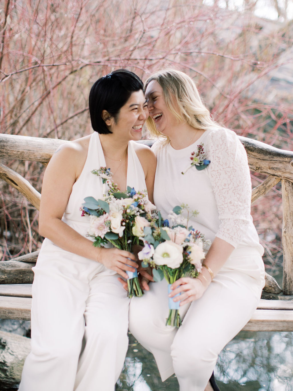 Post elopement ceremony, two brides sitting on natural wooden bench near Bow Bridge holding their bouquets; both appear to be laughing and giggling as if sharing a funny joke.