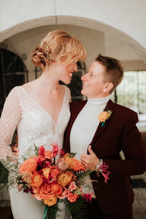 Close up shot of an LGBTQ couple looking at each other and smiling; one in a  maroon suit with cream turtleneck and the other with a beaded v-neck white wedding dress.