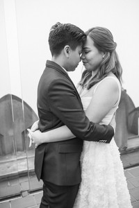 Black and white picture at the Top of the Rock of butch/femme Asian brides with their arms around each other and their foreheads touching are taking a moment to take the moment in; they have their eyes closed.
