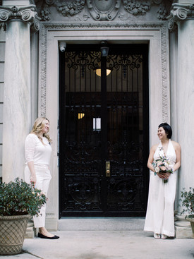 Two brides standing by the pillars of the entrance of an Upper West side building with a prominent black iron door; they're looking toward each other across the distance of the door; picture taken post elopement ceremony officiated by queer officiant at Once Upon A Vow.