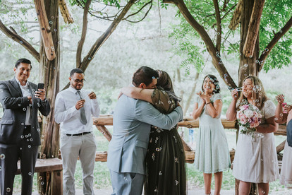 Photo of the bride and groom embracing in a hug once they are pronounced married by Spanish-speaking elopement officiant from Once Upon A Vow, the wedding party are blowing bubbles in celebration as one groomsman takes a photo on his phone