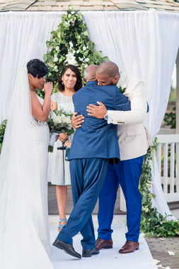 Groom hugging father of the bride while bride cries and officiant looks on right before the bilingual wedding ceremony officiated by Once Upon A Vow begins