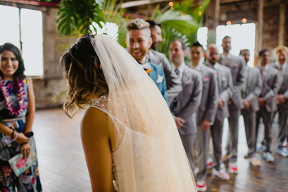 Photo of the bride reaching the groom with tropical arch, smiling officiant from Once Upon A Vow in the background, and groom and groomsmen in the background at Greenpoint Loft Brooklyn