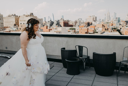 Picture of caucasian bride in white dress on NYC rooftop; it's a profile shot of her smiling; picture taken before ceremony officiated by lesbian officiant at Once Upon A Vow.