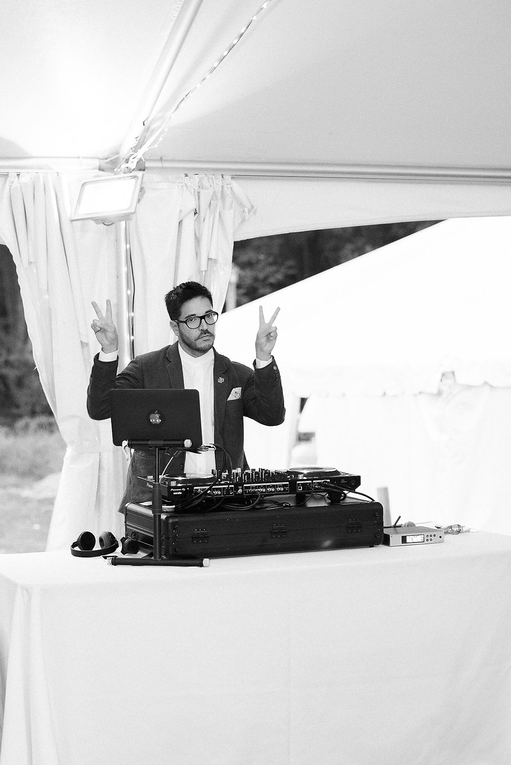 Black and white photo of a cool DJ from Empanadamn holding up the peace sign on both hands and his music set-up complete with a laptop at a New York City wedding