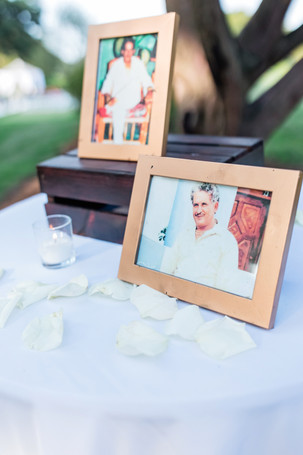 Focus on frame of white-haired man in honor of a deceased loved one set on a table with white rise petals and tea light candles organized by the Pelham Bay Golfcourse