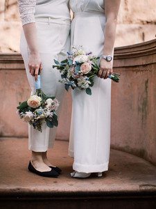 Close-up of bouquets; frame captures legs and hands; picture taken post elopement ceremony officiated by queer officiant at Once Upon A Vow.
