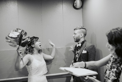 Black and white photo of couple and officiant from Once Upon A Vow in the elevator during the marriage license signing, bride excitedly raising the roof with tropical bouquet in one hand while husband looks at her and officiant laughs in the right corner while holding the clipboard and marriage license in Greenpoint Loft