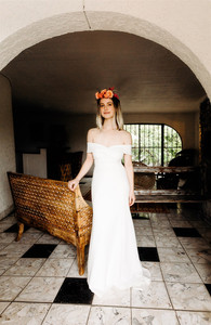 Bridal portrait of bride touching a straw chair wearing an off the shoulder white dress and a floral crown smiling calmly into the camera.