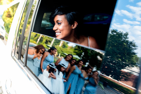 Smiling Dominican bride looking out limo window towards wedding party and in the car mirror reflection you can see the bridesmaids in blue dresses along with two flower girls before the bilingual wedding ceremony officiated by Once Upon A Vow
