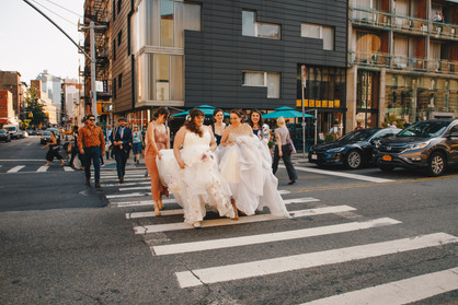 Two brides crossing Downtown NYC crosswalk with their wedding party crew behind them helping them keep the backs of their dresses from dragging on the floor; on their way to HousingWorks in Manhattan for their ceremony, which is officiated by Once Upon A Vow.