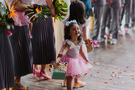 Photo of adorable flower girl dressed in a bright pink tutu with pom poms holding a cute pom pom basket where the ceremony officiated by Once Upon A Vow is taking place in Greenpoint Loft, Brooklyn