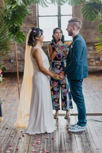 Photo of smiling officiant from Once Upon A Vow speaking to the couple as they hold hands and smile as the ceremony is upon ending, set in Greenpoint Loft, Brooklyn
