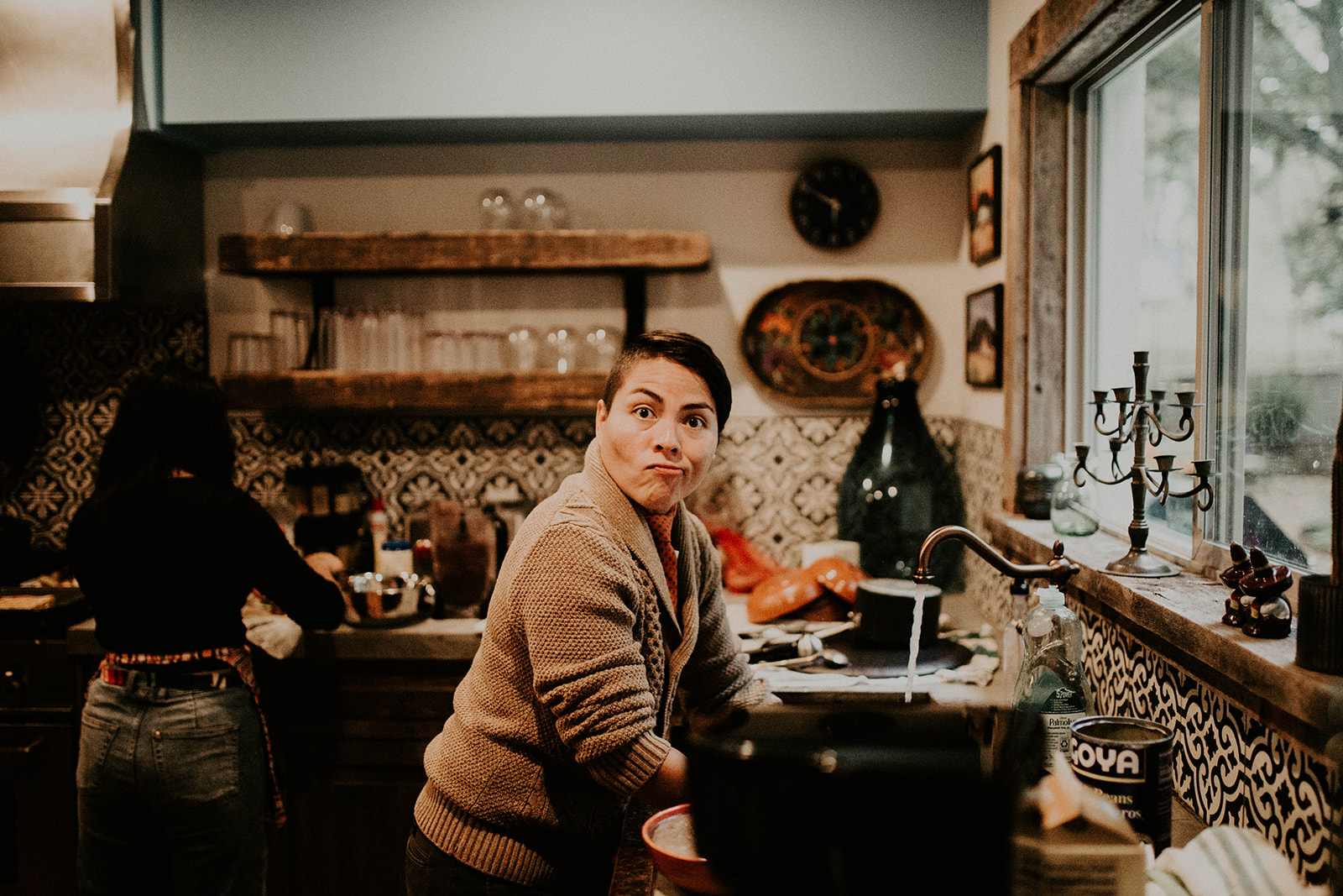 Photo of queer officiant from Once Upon A Vow making a funny face while helping in the kitchen