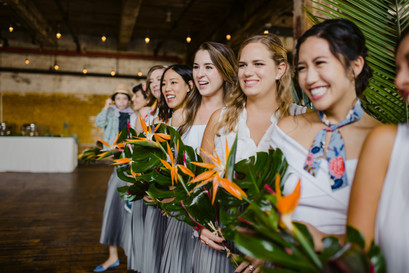 Photo of smiling bridesmaids holding beautiful tropical floral bouquets staring down the aisle as the bride walks towards them in Greenpoint Loft before the ceremony officiated by Once Upon A Vow begins.