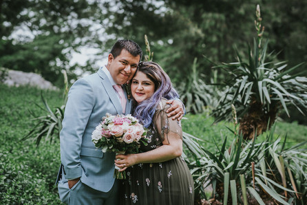 Sweet couple portrait looking into the camera of groom holding bride with left arm as the bride in her olive dress holds the bouquet with her left hand, the background is of pointed plant shrubbery set in Central Park